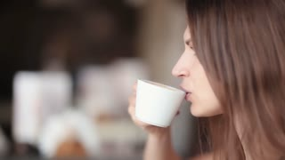 Side view of young brunette woman drinking coffee. Woman has a cup of coffee. Close-up