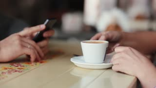 Side view of young woman drinking coffee. Woman has a cup of coffee. Hands of a man using his smartphone.