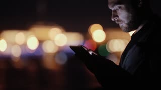 Sideview of a handsome man, smiling, nodding, using his tablet at night. Blurred city lights. Modern technology.