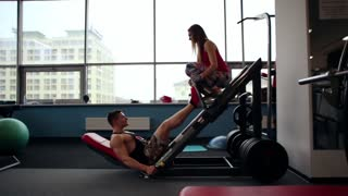Sideview of a male athlete doing leg press exercise, working out in a gym. An athletic woman sitting on the press.