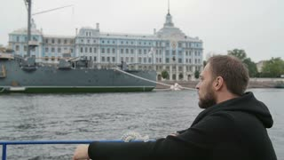 Sightseeing in St Petersburg. Handsome man explores, takes photos of the Cruiser Aurora, uses his smartphone, slow mo