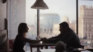 Silhouettes of lovers on a date sitting at the table. Nice view on the city street out of window of cafe on high floor.