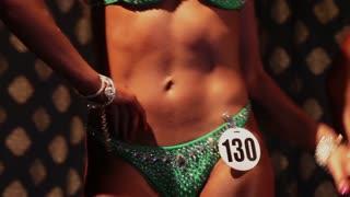 Slim female bodybuilder posing in bikini, fitness competition
