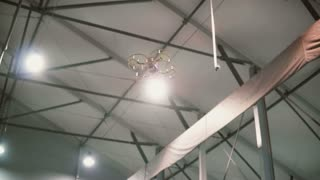 Small copter flies under the ceiling indoors. Drone flying over the floor.