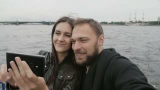Smiling beautiful couple uses smartphone, takes selfie on a river bus. Sightseeing in St Petersburg, bridge, slow mo