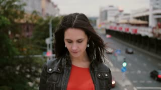 smiling beautiful girl standing on the bridge, touching her hair and looks at the camera. Wind blows her long hair. 4K