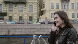 Smiling brunette girl using smartphone, talking on the phone. Happy woman on a boat tour, hanging up the phon, slow mo