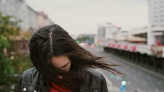 smiling girl standing on bridge touching her hair looking around then looks at the camera. Wind blows her long hair. 4K