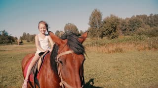 Smiling little girl riding a horse in the countryside on a sunny summer day. Slow mo