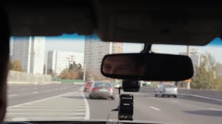Smiling man in a mirror while driving car in a city. Handsome mans face. Traveling by car.
