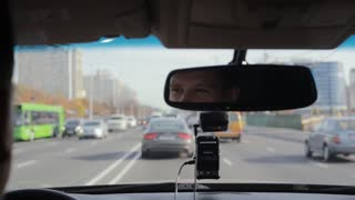 Smiling man in a mirror while driving car on a busy road in a city. Handsome mans face. Traveling by car.