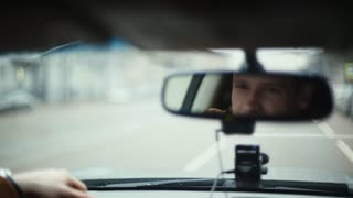 Smiling man in mirror while driving car in a city. Handsome mans face. Raindrops on the front window. Traveling by car.