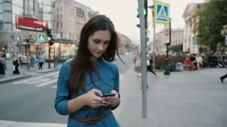 Smiling pretty woman in a blue denim dress talks on the phone in the centre of busy street. Slow mo