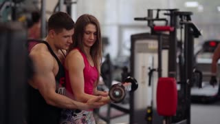 Sporty woman lifts dumbbells while working out in sport club. Athletic man is helping her to do the exercise correctly.