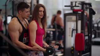 Sporty woman lifts dumbbells while working out in the gym. She is trying hard while exercising. Man helps her.