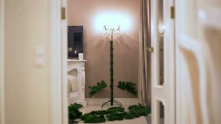 stop motion. gradually assembled an artificial Christmas tree, there are garlands illumination lights in a dark room.