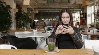 Stylish young woman with herbal tea uses a smartphone sitting at table in modern cafe, smiling. 4K