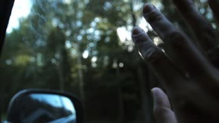 Sun rays through fingers and trees. Hand with rings on window of car on the go. Fingers palm. Close-up. Slow mo