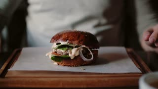 Tasty burger is great on a wooden tray. A man takes his hands and eats, try the taste