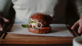 Tasty burger is great on a wooden tray. A man takes his hands and was going to eat.