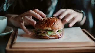 Tasty burger is great on a wooden tray. A woman takes his hands and was going to eat.