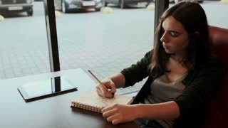 Teenage student makes sketches in notebook in cafe