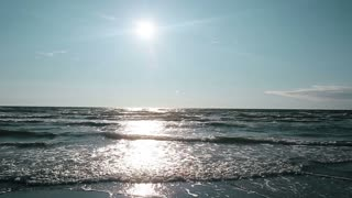 The bright sun in blue sky shines on the surface of the sea and the waves sparkle in the light.