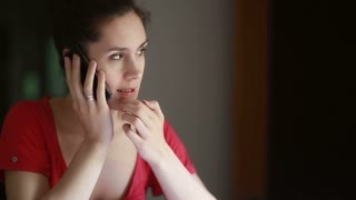 thoughtful girl talking on phone at home lifestyle