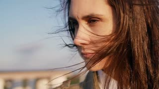thoughtful young beautiful woman standing on the roof at the sunset, her long dark hair blowing wind. slow motion.