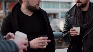 Three handsome men with beards having conversation and coffee outside. Slow mo