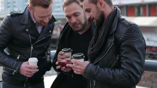 Three handsome young men with beards smiling and taking selfie. Good-looking guys using a smartphone. Slow mo