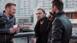 Three handsome young men with beards talk, smile and have coffee on the go near a bridge railing in the city. Slow mo
