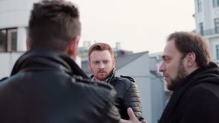 Three men with beards talk. A young red-haired man in the centre, two other stand with their backs to camera. Slow mo