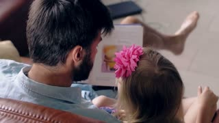 top view. young father and his little blond daughter are reading a story on leather sofa in the dining room. 4K