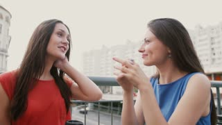 Two attractive brunette women best friends drinking coffee in cafe and talking after shopping. 4k
