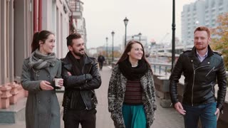 Two beautiful girls and two stylish men walk in the city, talk emotionally, smile. Slow mo, steadicam shot