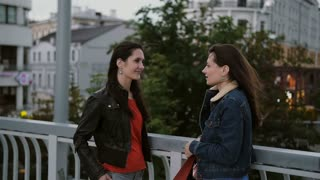 Two beautiful girls best friends standing on the city bridge, talking, smiling, laughing. slow mo. stedicam shot