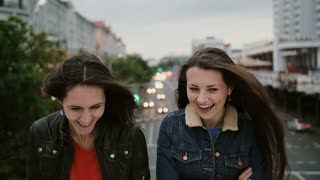 Two beautiful girls standing on the bridge, smiling, laughing and looks at the camera. Wind blows they long hair.