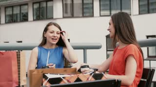 Two beautiful women drinking coffee in cafe and talking after shopping. 4k
