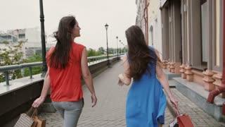 Two beautiful young woman friends walking with shopping bags, talking having fun, back view, slow mo stedicam shot