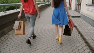 Two beautiful young woman friends walking with shopping bags, talking having fun, back view, slow mo stedicam shot