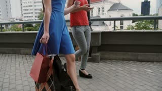 Two beautiful young woman friends walking with shopping bags, talking having fun, side view, slow mo stedicam shot