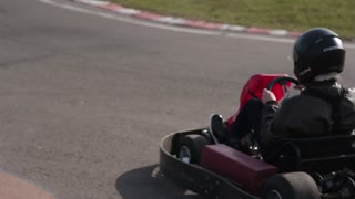 Two drivers in karts are moving very slowly on a ride. Go kart track.