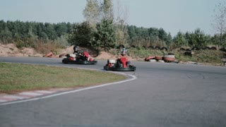 Two drivers on a go-kart track move into the camera and pass it by. Go-kart race.