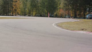 Two drivers on a go-kart track pass by the camera. Go-kart race.