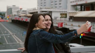 Two girls best friends taking selfie, standing on the city bridge, talking, smiling, laughing. 4K