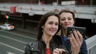 Two girls best friends taking selfie, standing on the city bridge, talking, smiling, laughing. slow mo.