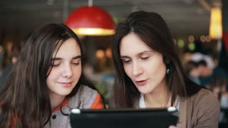 two girls sisters using tablet talking in cafe