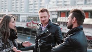 Two handsome men and a beautiful girl talk standing near a bridge railing. Girl is surprised, then smiles. Slow mo