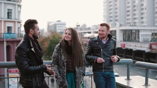 Two handsome young men and a pretty girl talk on the bridge. Friends chat and smile, view of cars on the road. Slow mo